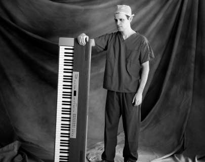 Comedian Adam Kay wearing doctor's scrubs standing holding an upended keyboard