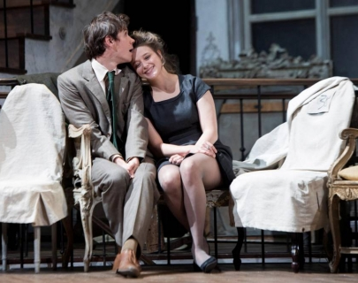 Two actors sat on stage next to two chairs covered in white sheets. They are both smiling and the man is kissing the woman's forehead