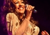 Sheila Ferguson singing into a microphone, wearing a gold dress.