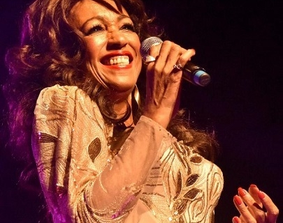 Sheila Ferguson singing into a microphone, wearing a gold dress.