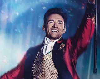 Actor Hugh Jackman dressed in a showman's red velvet jacket and smiling at the camera