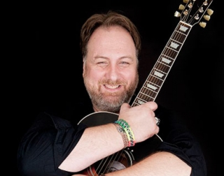 Mitch Benn holding a guitar and smiling against a black background