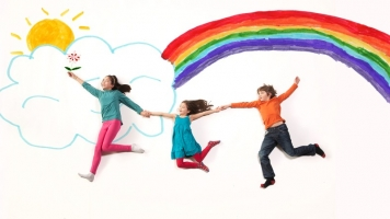 Three kids holding hands on a rainbow doodle background