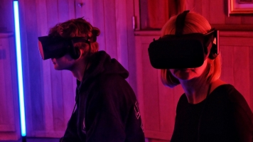 Two people with VR headsets surrounded by red lights