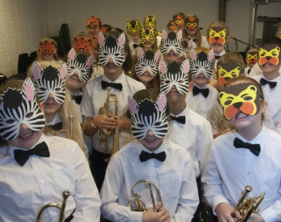 A group of young musicians holding instruments and wearing animal masks