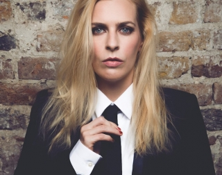 Comedian Sara Pascoe wearing a suit and leaning against a brick wall