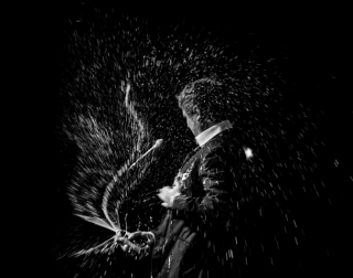 A black and white image of comedian Tim Key opening a bottle of champagne