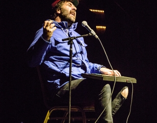 David O'Doherty sitting on stage with a keyboard on his lap