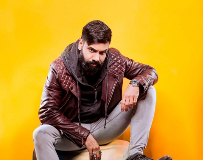 Comedian Paul Chowdhry sitting against a yellow background
