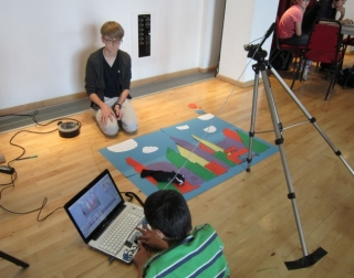 Two kids with filming equipment and a laptop