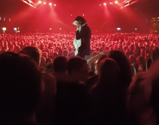 Man dressed in black holding a white cloth standing in the middle of a crowd in red lighting
