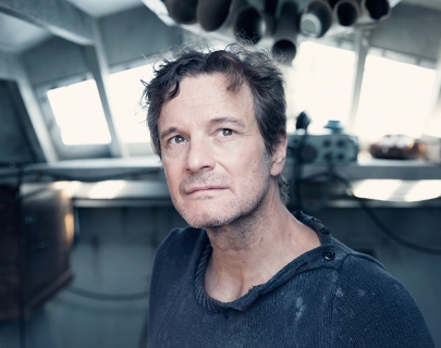 Image of Colin Firth wearing a navy jumper standing in a boat