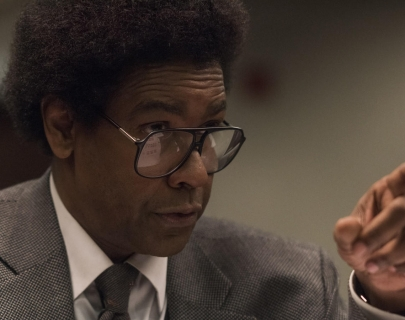 Actor Denzel Washington wearing a grey suit and big glasses pointing his index finger