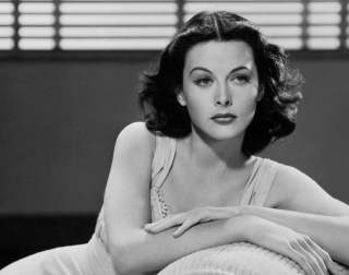 A black and white image of Hedy Lamarr sitting on a sofa