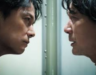 Two men facing each other through glass
