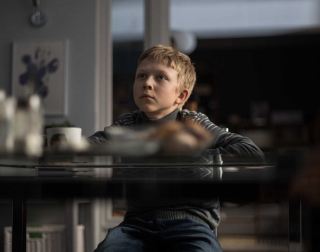 Blonde kid sitting at a table