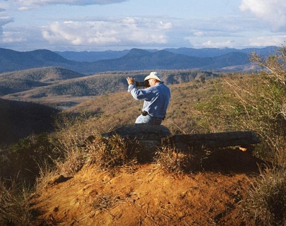 An image of a man with a large camera taking a photo of a mountain landscape