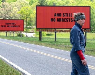 Frances McDormand wearing a blue jumpsuit standing in front of two bright red billboards.