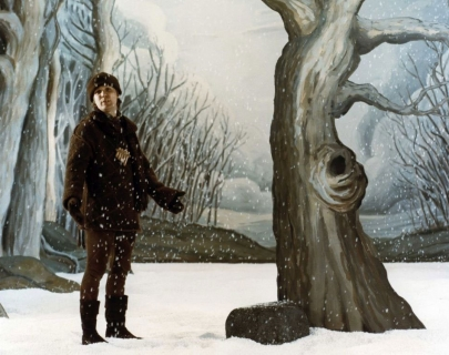 A man stands in the snow next to a tree