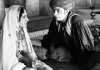 A man looks intensely at a woman in traditional Indian clothes