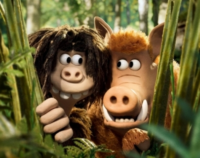 A claymation boy and hog peer through some bushes.