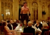 A shirtless man standing on a dining table in a crowded hall