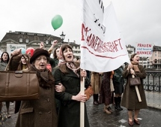 Women wearing long coats march and carry banners