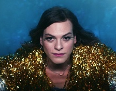 A woman in a gold and silver sparkly top, wearing false eyelashes on a blue background looks into the camera