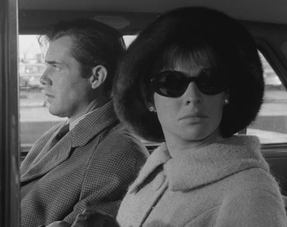 A man and a woman sitting in a car. The woman is looking out the window wearing sunglasses