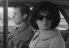 A man and a woman sitting in a car. The woman is looking out the window wearing sunglasses.