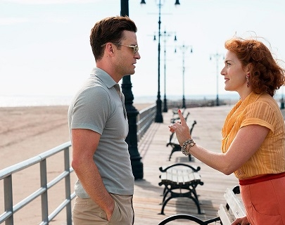 A man and a woman in 1950s clothing talk on a promenade next to a beach.