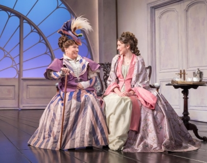Two actresses in Victorian gowns sitting on stage