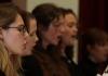 Close shot of four girls wearing black and singing