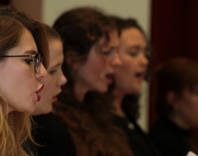 Close shot of four girls wearing black and singing