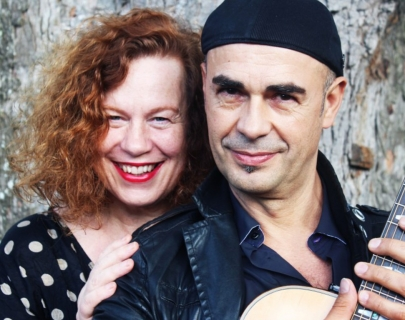SaraSarah Jane Morris hugging Antonio Forcione from behind while he holds a guitar