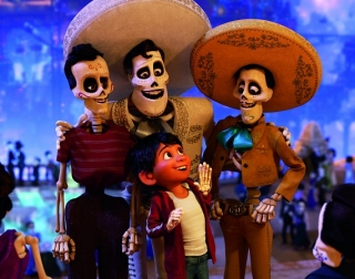 Three smiley skeletons wearing sombreros and mariachi clothes surrounding a boy wearing a white t shirt and a hoodie