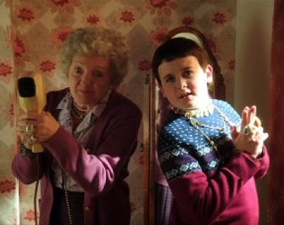 A young boy and his granny stand back to back in front of a floral wallpaper, pretending to hold guns.