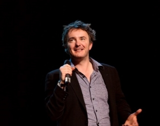 Comedian Dylan Moran holding a microphone and smiling