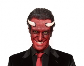 Comedian Marcus Brigstocke dressed up as the devil with red skin and horns on his forehead