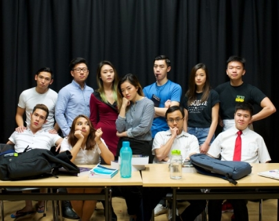 Group of students around a table against a black background