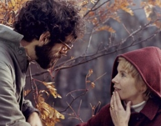 A woman with short blonde hair, wearing a red coat, talks to a man with curly, dark hair and glasses outside on a Autumn day.