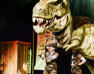 Two actors dressed as explorer with a T-Rex behind them