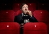 Comedian Andrew Maxwell dressed in black sitting on red cinema seats eating popcorn