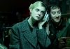 Actress Elle Fanning wearing a tweed coat and listening to music on big white earphones that she is sharing with a young man
