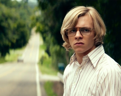 A young blonde teen wearing glasses and a shirt standing on the side of a road