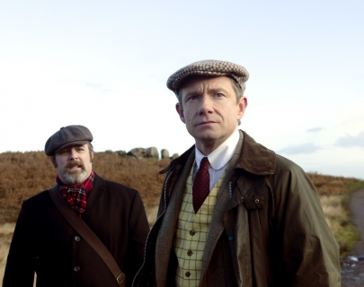 Two men in flat caps and heavy jackets stand in front of a hill, looking out to the distance