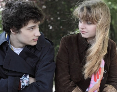 Close up of a young boy and girl sitting in a park looking at each other