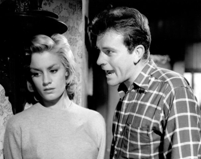 Black and white. A man in a checked shirt shouts at a blonde woman.