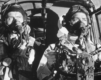 Black and white. Two men sit in the cockpit of a plane in World War 2.
