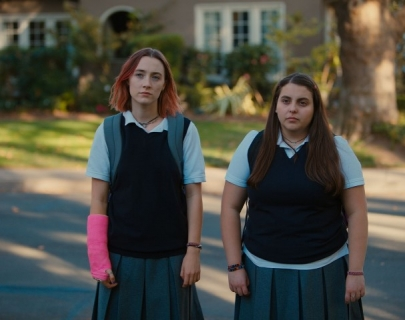 Two girls in school uniform stand on a suburban street.